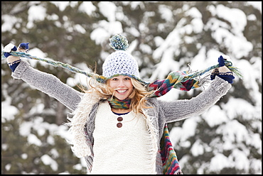 USA, Utah, Salt Lake City, portrait of young woman in winter clothing pulling hat strings