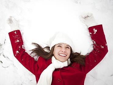 USA, Utah, Lehi, Young woman lying in snow