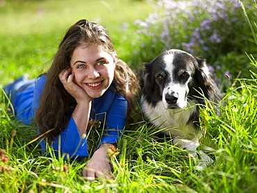 USA, Colorado, Portrait of young woman relaxing with dog on grass