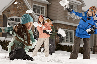 USA, Utah, Provo, Boys (10-11, 12-13) and girls (10-11, 16-17) having snow ball fight in front of house