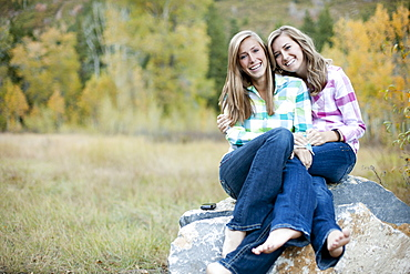 USA, Utah, Sundance, Portrait of two young women sitting on boulder