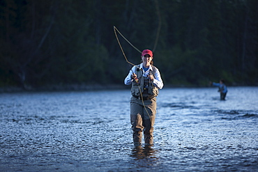 Canada, British Columbia, Fernie, Portrait of woman fly fishing in river