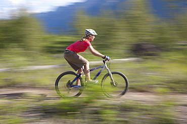 Canada, British Columbia, Fernie, Young woman riding on mountain bike