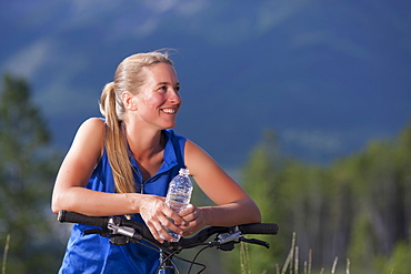 Canada, British Columbia, Fernie, Mid adult woman leaning against bike handlebar and drinking water