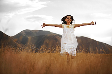 Girl (10-11) running through wheat field