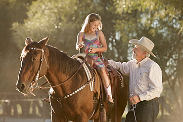 Senior man assisting granddaughter (8-9) horseback riding in ranch