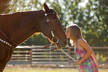 Cowgirl (8-9) kissing horse in ranch