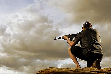 Man aiming gun on rocks