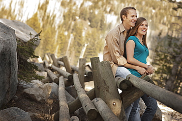 Happy couple sitting on log fence