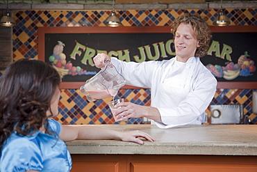 Bartender pouring drink at juice bar