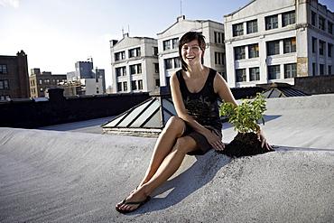 Woman sitting on rooftop beside aspen sapling