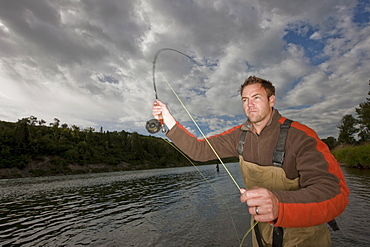 Fly fisherman casting