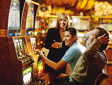 People in casino playing on slot machines