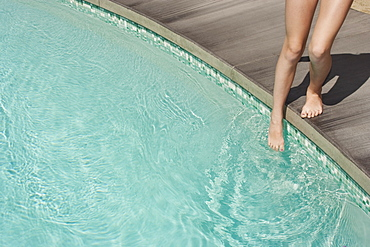 Teenage girl entering swimming pool