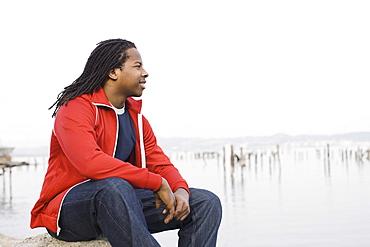 Teenage boy (16-17) with dreadlocks, sitting at waterfront, San Francisco, California, USA
