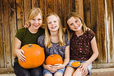 Girls holding pumpkins