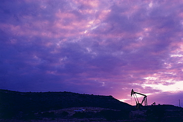Oil rig in distance under sunset sky