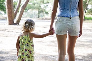 Rear view of mother and daughter (2-3) holding hands, Nationaal Park De Loonse en Drunense Duinen, The Netherlands