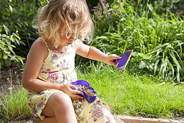 Little girl (2-3) playing in sandbox, Helvoirt, The Netherlands