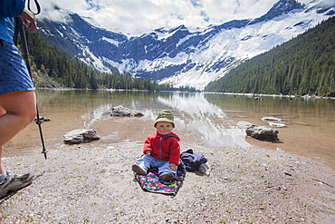 Boy (4-5) sitting on lakeshore, Avalanche Lake, Glacier National Park, Montana, USA