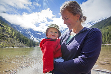 Portrait of woman with son (4-5) on lakeshore, Avalanche Lake, Glacier National Park, Montana, USA