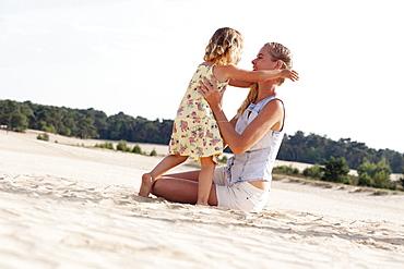 Mother playing with daughter (2-3) at sandy beach, Nationaal Park De Loonse en Drunense Duinen, The Netherlands