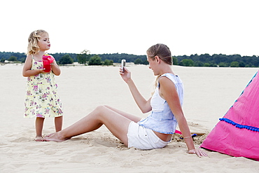 Mother taking picture of daughter (2-3) on beach, Nationaal Park De Loonse en Drunense Duinen, The Netherlands