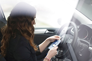 Young woman sitting in car and holding parking ticket