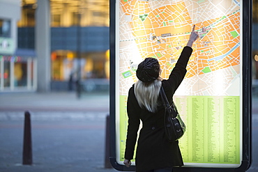 Young woman pointing at city map