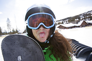 Girl with snowboard sticking out her tongue, USA, Montana, Whitefish