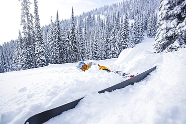 Male skier lying on snow, USA, Montana, Whitefish