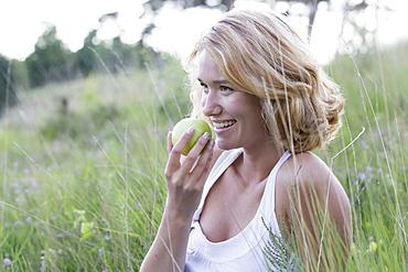 Portrait of happy woman eating apple, Netherlands, Gelderland, Hatertse Vennen
