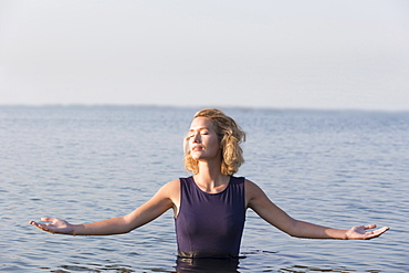 Beautiful woman standing in lake with arms outstretched