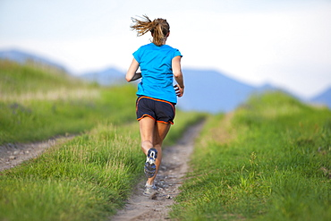 Rear view of young woman jogging, Kalispell, Montana, USA