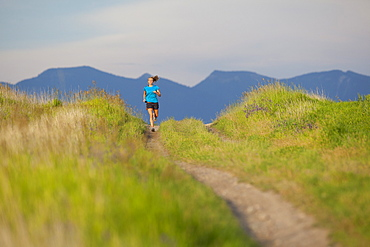 Distant view of young woman jogging, Kalispell, Montana, USA