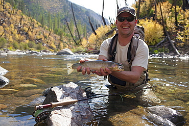 Fisherman showing fresh trout, North Fork Blackfoot River, Montana, USA