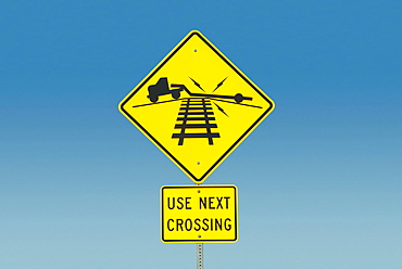 Yellow road sign depicting truck on railroad crossing