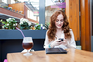 Elegant woman in cafe using mobile phone, Goirle