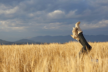 Woman lying in scenic field with feet in air, Whitefish, Montana, USA