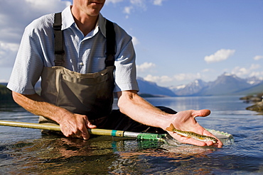 Man holding juvenile western cutthroat trout, Lake McDonald, Glacier National Park, Montana, USA
