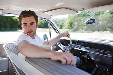 Young man in vintage car, Netherlands, Tilburg