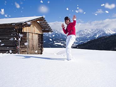 Austria, Maria Alm, Woman at top of mountain enjoying snowball fight, Austria, Maria Alm