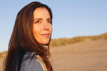 Portrait of woman standing against sand dune