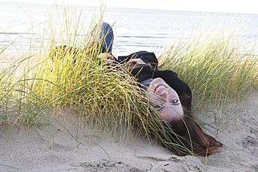 Netherlands, Zeeland, Haamstede, Woman lying on sand dune, Netherlands, Zeeland, Haamstede