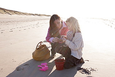 Mother with daughter collecting shells on beach