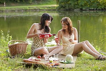 France, Picardie, Albert, Young women having picnic on lakeside, France, Picardie, Albert