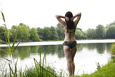 France, Picardie, Albert, Young woman in bikini standing on lake shore, France, Picardie, Albert