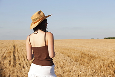 France, Picardie, Albert, Young woman in straw hat looking at country landscape, France, Picardie, Albert