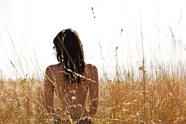 Young woman standing among cornfield