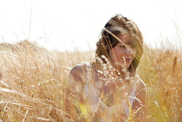 Young woman sitting on cornfield